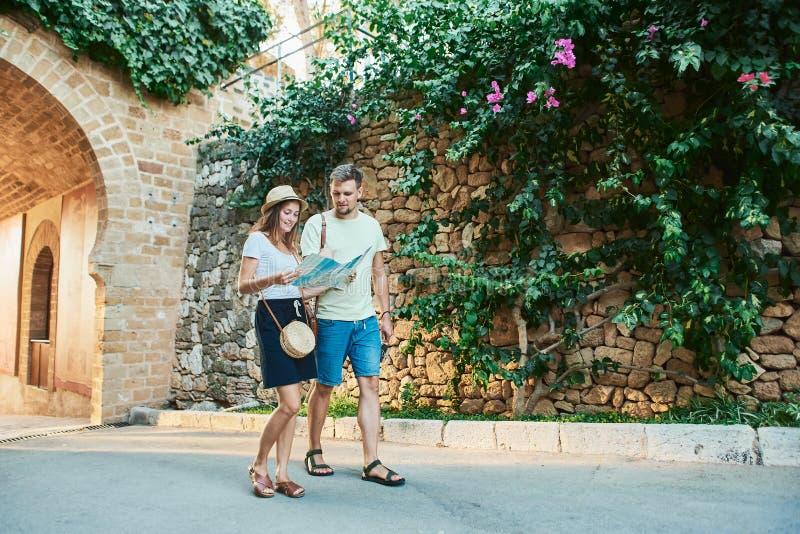 Jeunes couples heureux des voyageurs tenant la carte dans des mains image stock