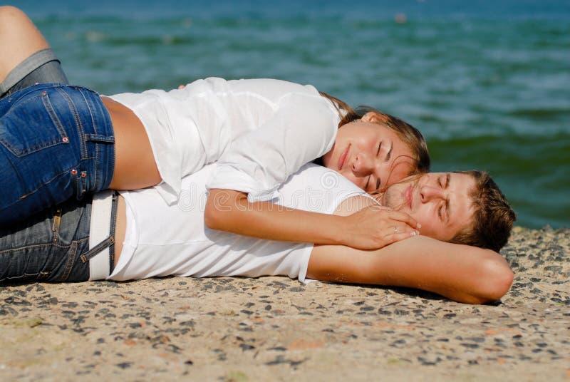 Jeunes couples heureux embrassant sur la côte photographie stock libre de droits
