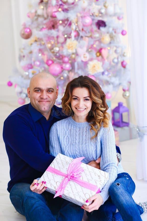 Jeunes couples heureux européens se reposant près de l'arbre de sapin rose décoré avec le présent image stock