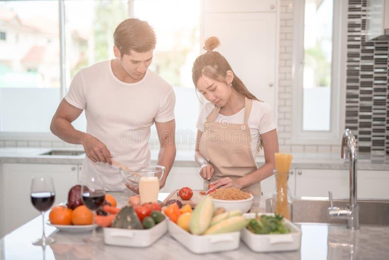 Jeunes couples heureux faisant cuire ensemble dans la cuisine à la maison image stock