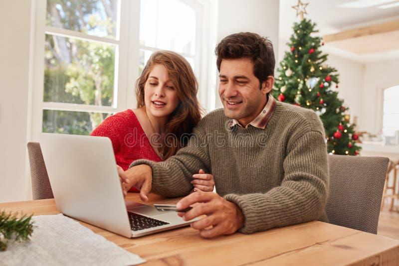 Jeunes couples heureux faisant des emplettes en ligne pour Noël photos libres de droits