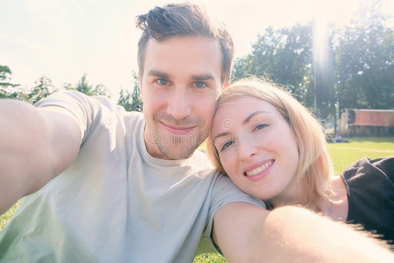 Jeunes couples heureux faisant le selfie photos stock