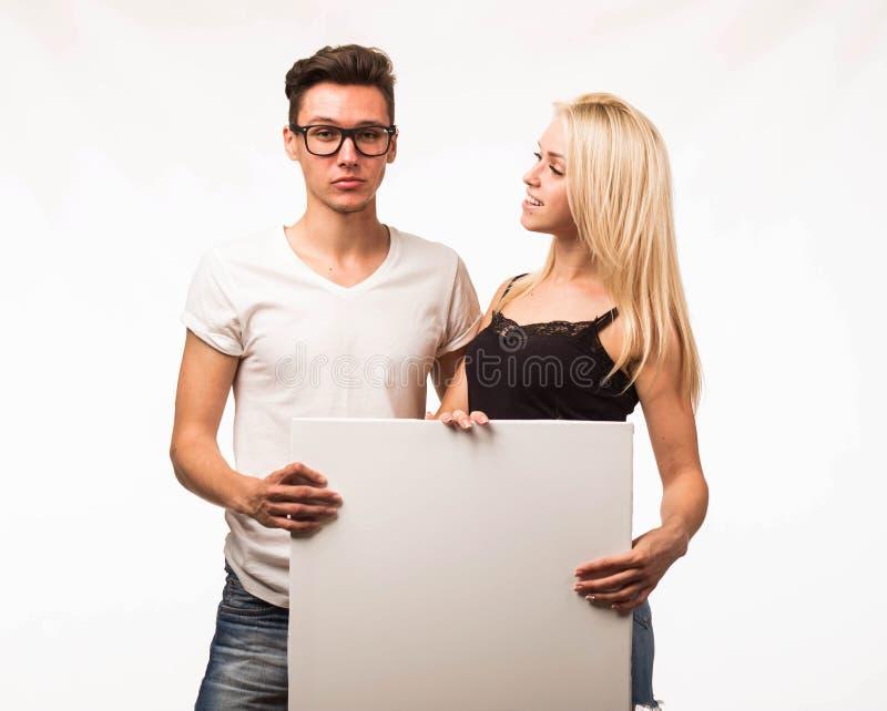 Jeunes couples heureux montrant la présentation dirigeant la plaquette photos stock