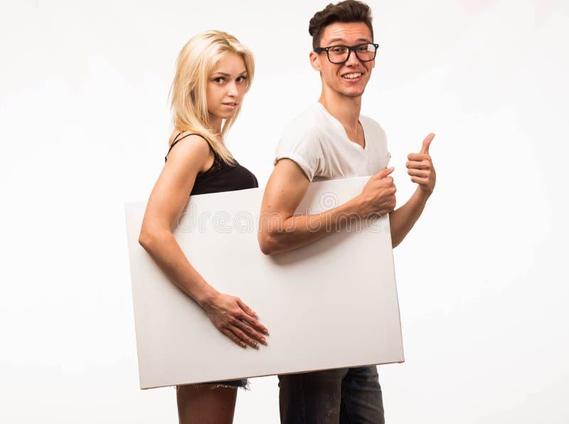 Jeunes couples heureux montrant la présentation dirigeant la plaquette images libres de droits