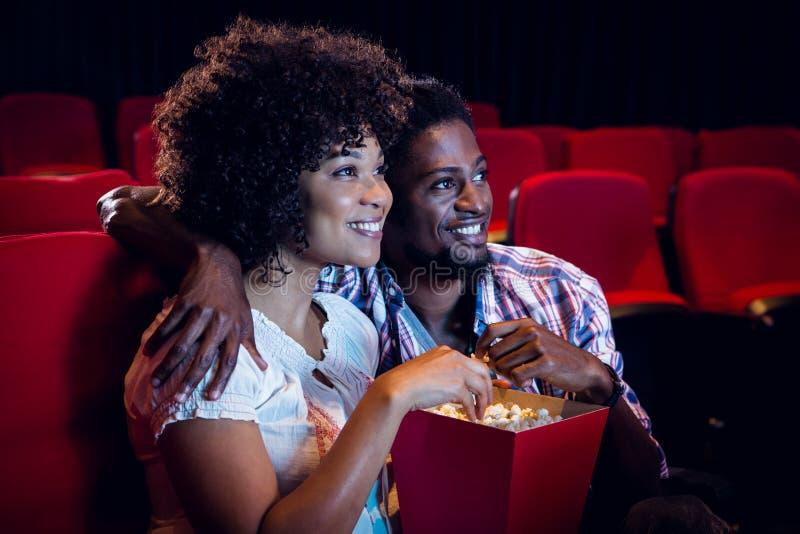 Jeunes couples heureux observant un film photos stock