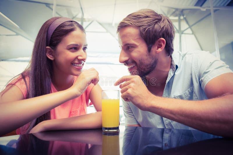 Jeunes couples heureux partageant une boisson photos stock