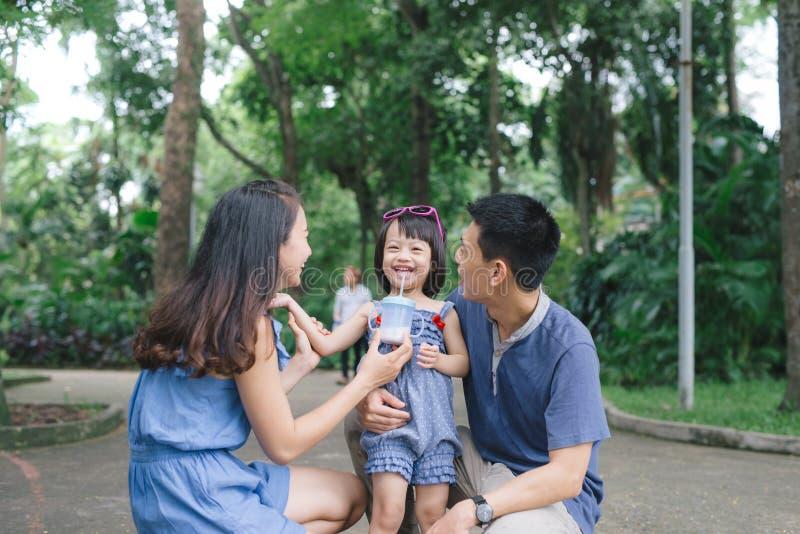 Jeunes couples heureux passant le temps avec leur fille photographie stock libre de droits