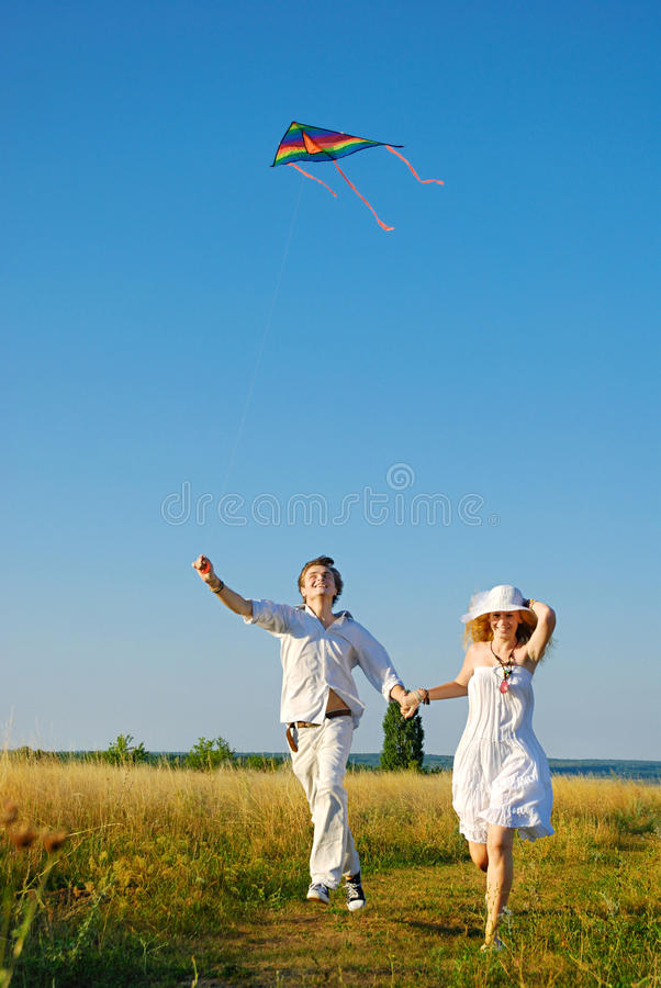 Jeunes couples heureux pilotant un cerf-volant photographie stock libre de droits