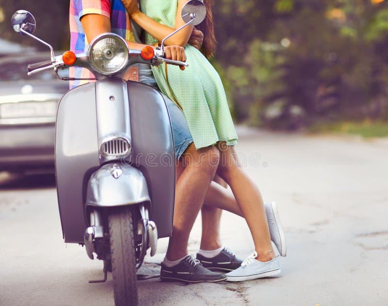 Jeunes couples heureux près du vieux rétro scooter dans une rue de ville photos stock