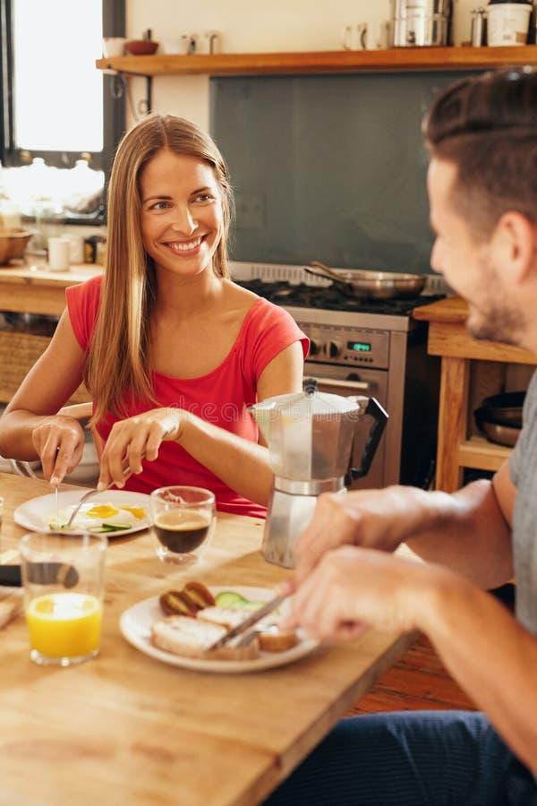 Jeunes couples heureux prenant le petit déjeuner à la maison images libres de droits