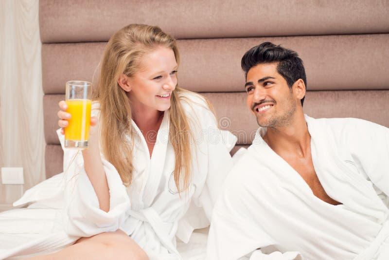 Jeunes couples heureux prenant le petit déjeuner dans la chambre d'hôtel de luxe image stock