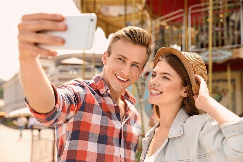 Jeunes couples heureux prenant le selfie près du carrousel en parc images libres de droits