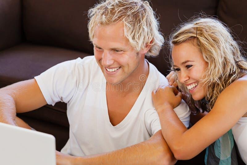 Jeunes couples heureux regardant l'ordinateur portable photo stock