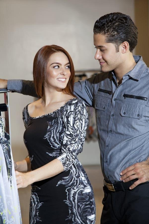Jeunes couples heureux regardant l'un l'autre tout en faisant des emplettes dans la boutique de mode images stock