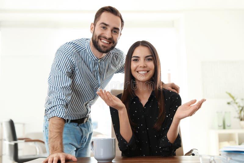 Jeunes couples heureux regardant la caméra et employant la causerie visuelle photo libre de droits