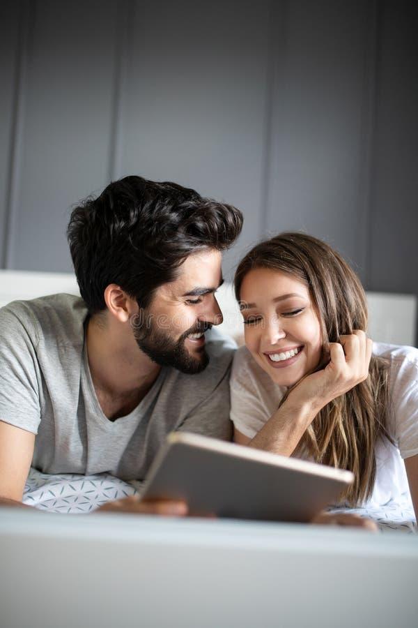 Jeunes couples heureux regardant un comprimé ensemble et riant tout en se trouvant sur le lit images stock