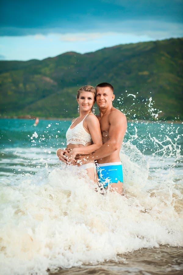 Jeunes couples heureux riant et étreignant dans l'eau de vague de mer sur la plage photos stock