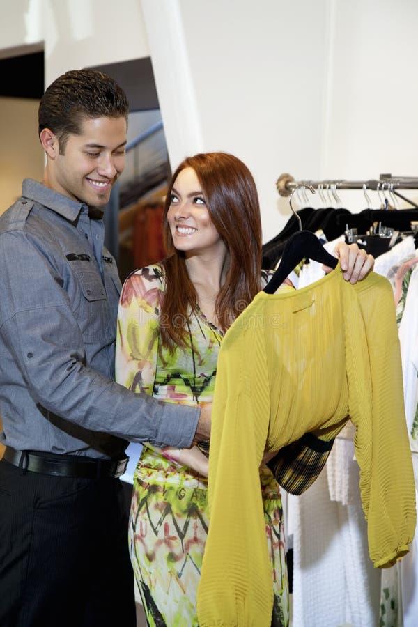 Jeunes couples heureux sélectionnant une robe ensemble dans la boutique de mode photo libre de droits