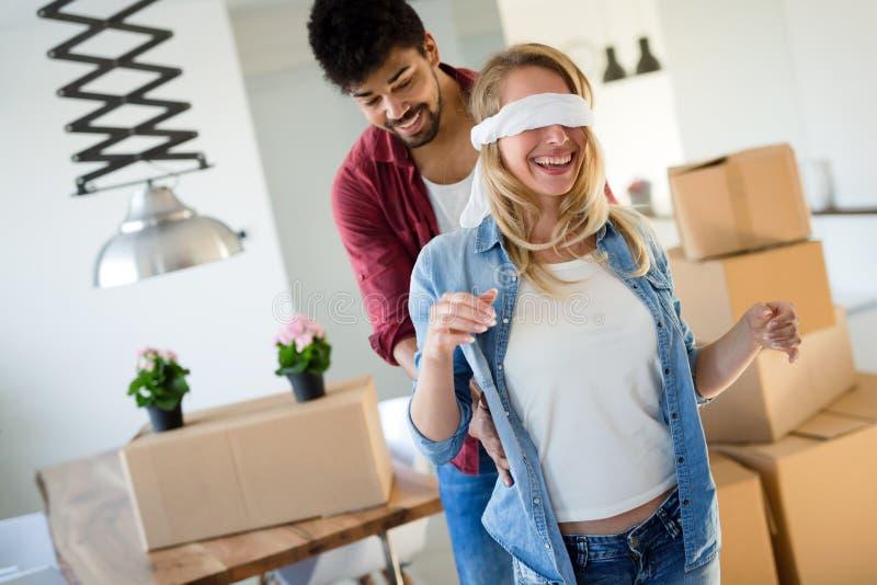 Jeunes couples heureux se déplaçant la nouvelle maison et déballant des boîtes photos libres de droits