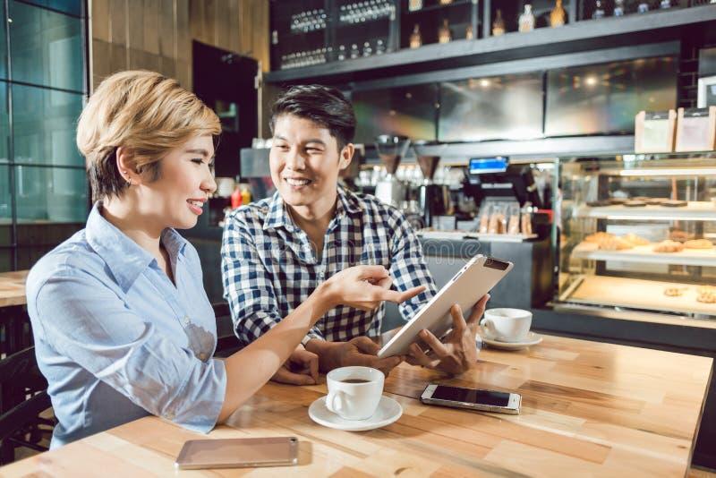 Jeunes couples heureux se reposant dans le café images stock