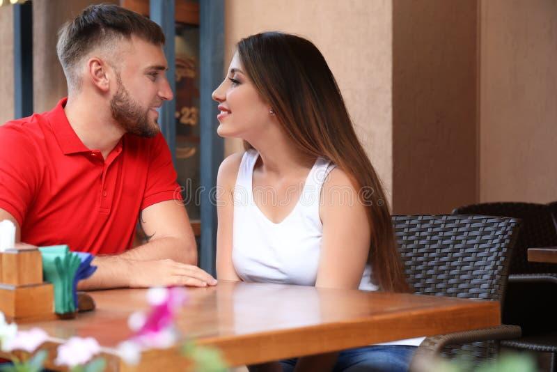 Jeunes couples heureux se reposant en café dehors photographie stock libre de droits
