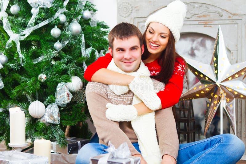 Jeunes couples heureux se reposant par l'arbre de Cristmas images stock