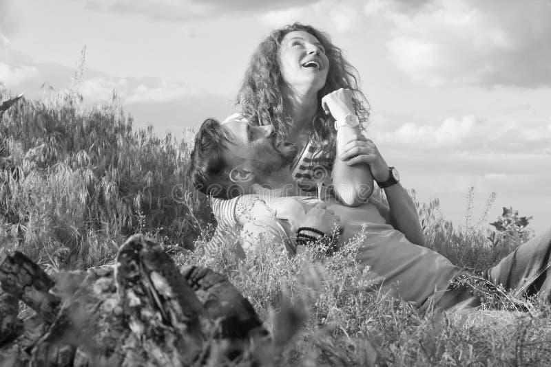 Jeunes couples heureux se reposant par le feu l'herbe et en étreignant Montres d'amours de couples photographie stock libre de droits