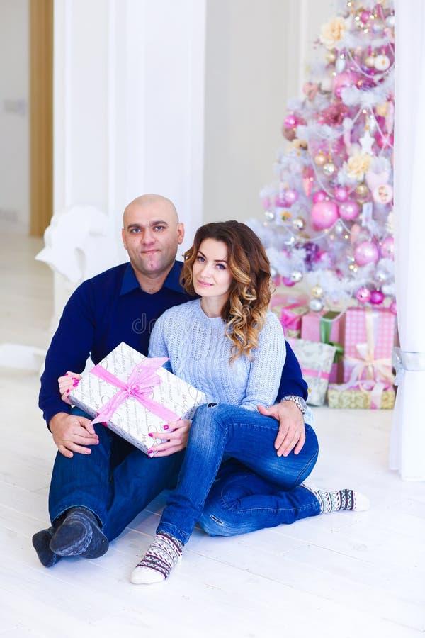 Jeunes couples heureux se reposant près de l'arbre de sapin rose décoré avec le présent photo libre de droits