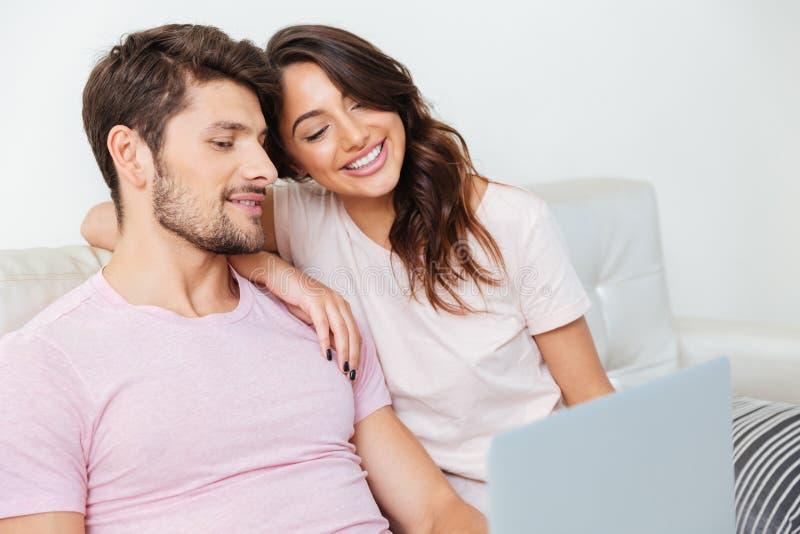 Jeunes couples heureux se reposant sur le divan utilisant l'ordinateur portable photos stock