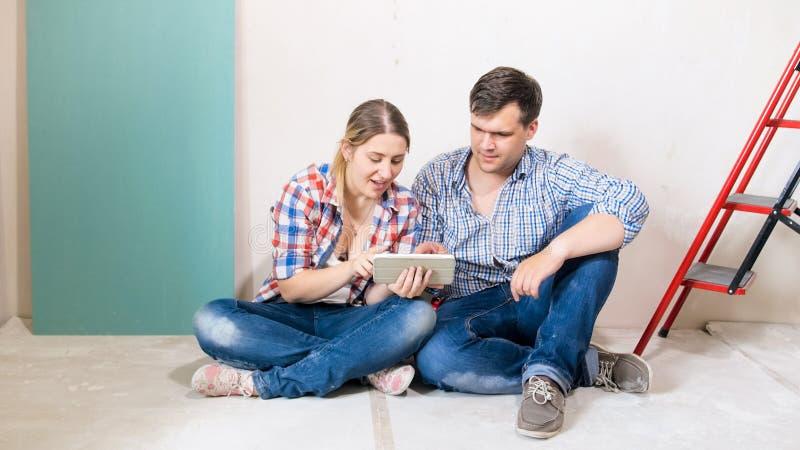 Jeunes couples heureux se reposant sur le plancher à la maison sous l'Internet de rénovation et de lecture rapide sur le comprimé photos libres de droits