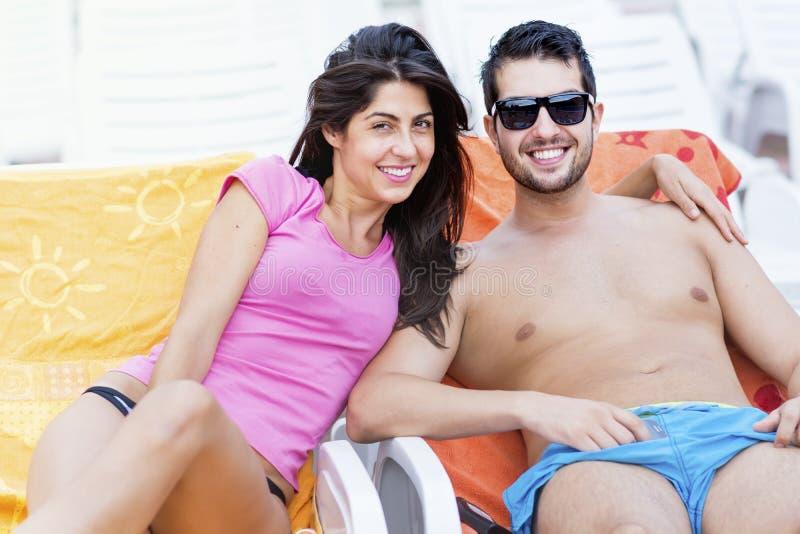 Jeunes couples heureux souriant, étreignant et détendant sur la piscine photographie stock