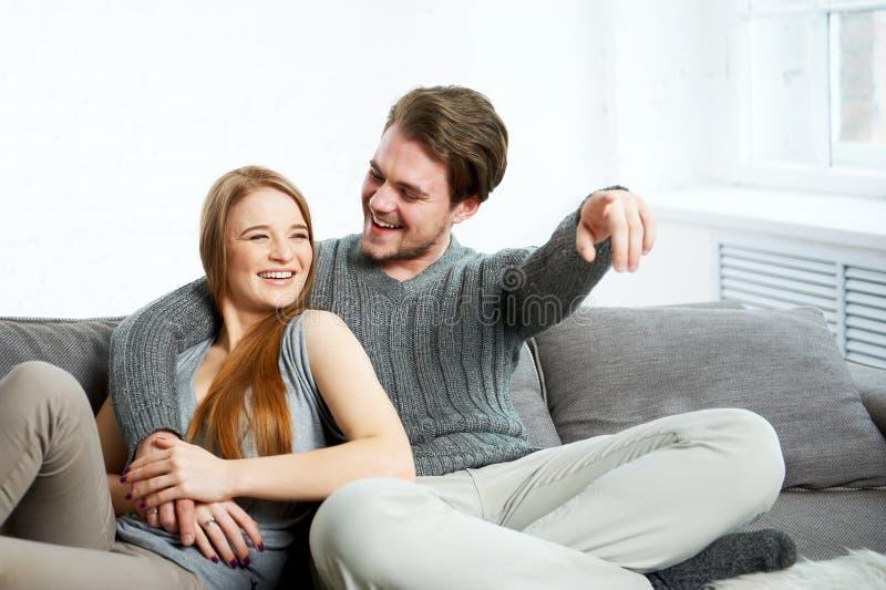 Jeunes couples heureux sur le sofa regardant la TV photographie stock libre de droits