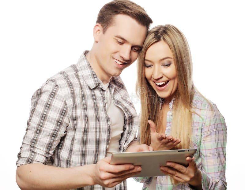 Jeunes couples heureux tenant l'ordinateur de PC de comprimé images libres de droits