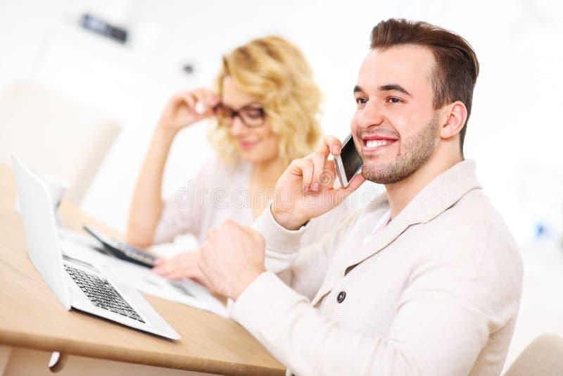 Jeunes couples heureux travaillant sur des documents à la maison image stock