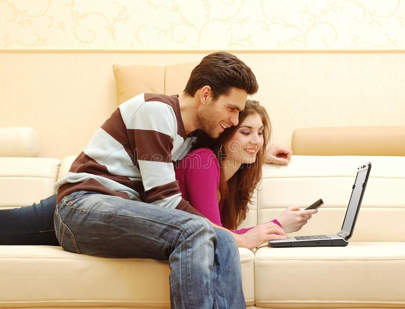Jeunes couples heureux travaillant sur l'ordinateur portatif images libres de droits