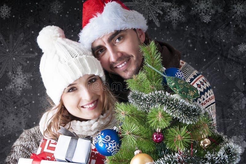Jeunes couples heureux W près de l'arbre de Noël. image libre de droits