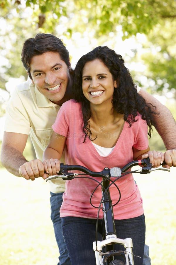 Jeunes couples hispaniques faisant un cycle en parc photos stock