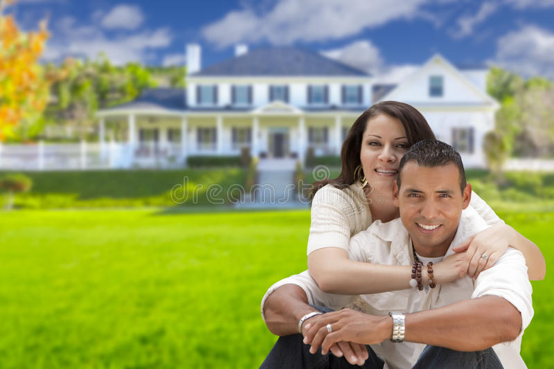 Jeunes couples hispaniques heureux devant leur nouvelle maison images stock