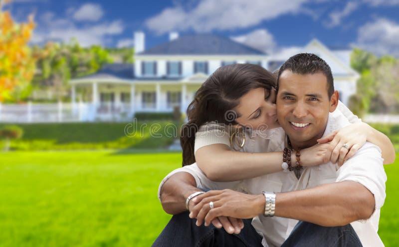 Jeunes couples hispaniques heureux devant leur nouvelle maison photographie stock libre de droits