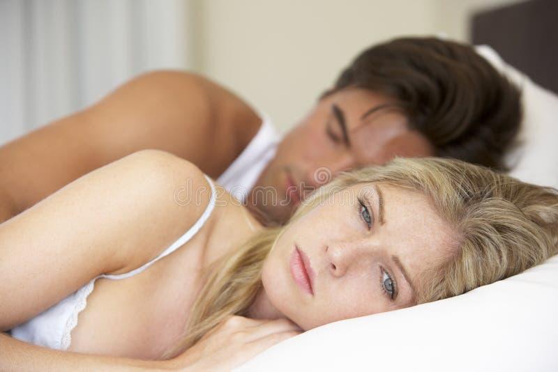Jeunes couples inquiétés dans le lit photos libres de droits