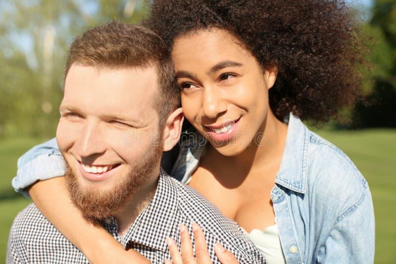Jeunes couples interraciaux affectueux dehors la journée de printemps image libre de droits