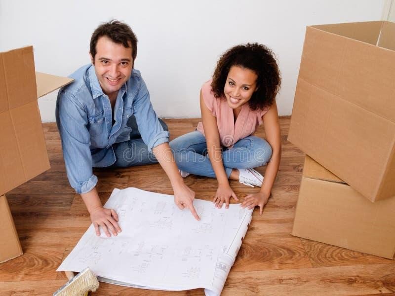 Jeunes couples interraciaux prêts pour la relocalisation à la maison images libres de droits