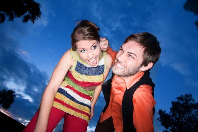 Jeunes couples jouant autour au coucher du soleil photos libres de droits