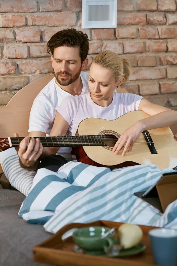 Jeunes couples jouant la guitare dans le lit photos stock