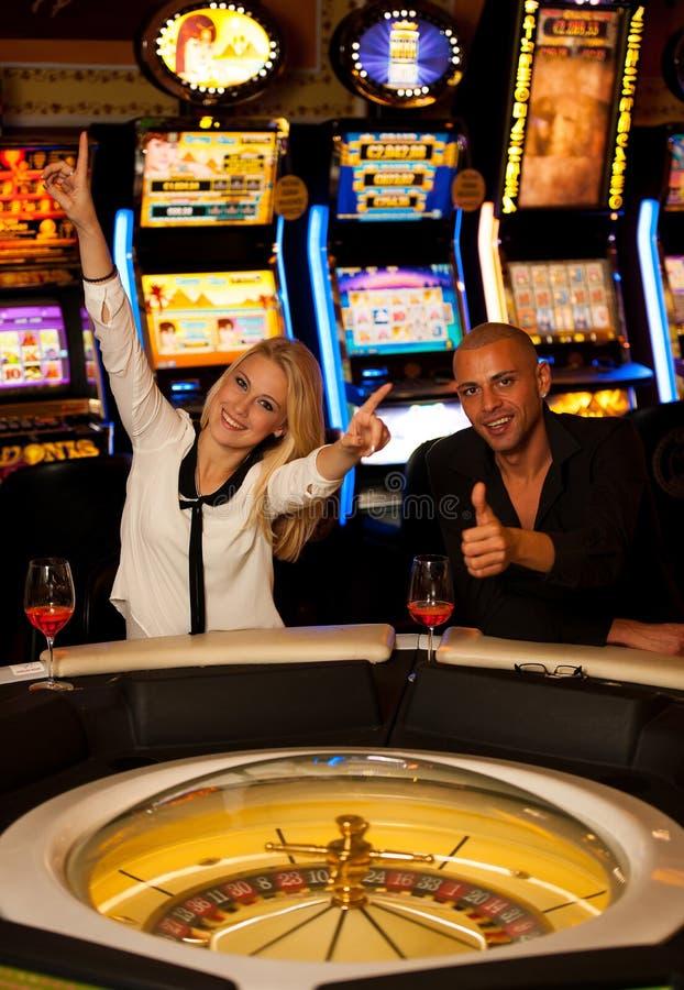 Jeunes couples jouant la roulette dans le casino pariant et gagnant photos libres de droits