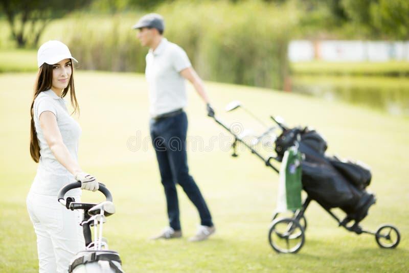 Jeunes couples jouant le golf photos libres de droits