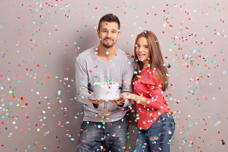 Jeunes couples joyeux tenant un gâteau d'anniversaire images stock