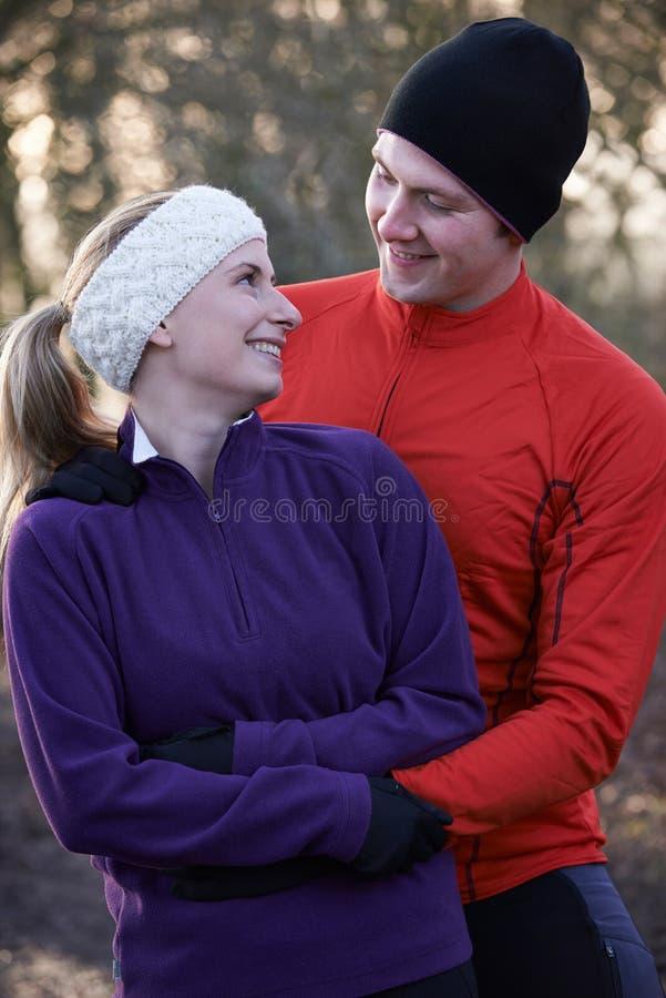 Jeunes couples l'hiver couru par la région boisée images libres de droits