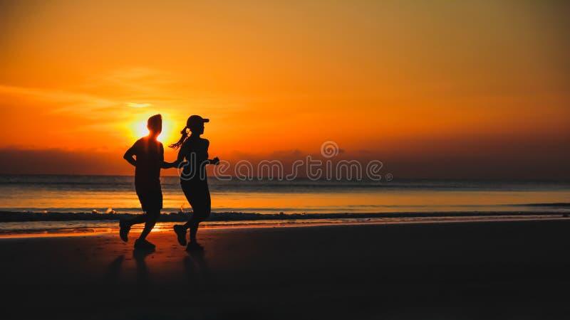 Jeunes couples : l'homme et la femme courent ensemble sur un coucher du soleil sur le lac photos stock