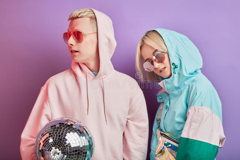 Jeunes couples ? la mode des danseurs posant avec la boule de disco sur le fond violet photographie stock libre de droits